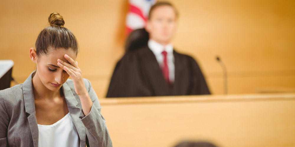 Stressed lawyer with head bowed in the court room