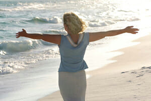 Girl with arms outstretched at beach.