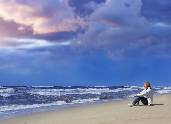 adult woman on the beach watching the stormy sea